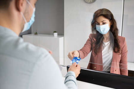 Shop Cashier In Store Or Hotel Reception With Medical Mask