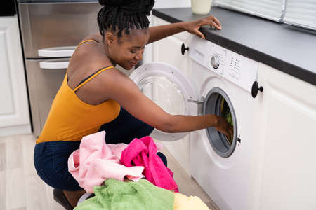 Woman Loading Dirty Clothes In Washing Machine For Washing In Utility Room Imagens