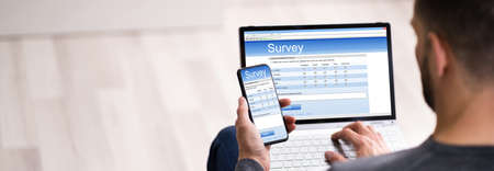 Close-up Of A Man Filling Online Survey Form On Laptop And Smartphone
