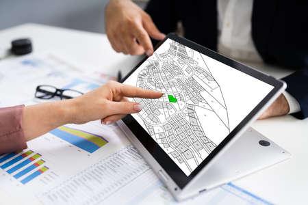 People Using Cadastral Survey Map On Tablet Screen Foto de archivo