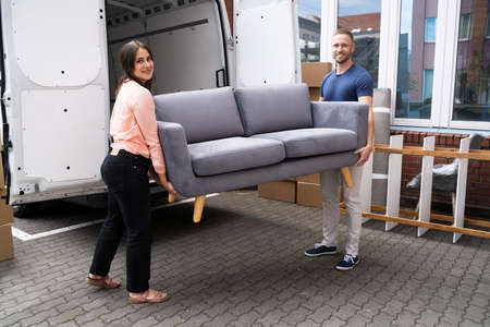 Couple Moving Couch Or Sofa Together. Furniture Movers
