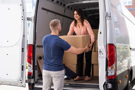 Couple Moving Boxes From Van Or Truck Together Outdoors Stock Photo