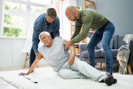 Helping Elder Senior Fallen Man After Fall Accident Foto de archivo