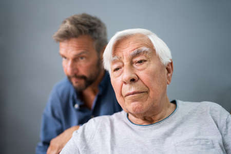 Old Senior Man With Alzheimer Getting Support And Care From Son