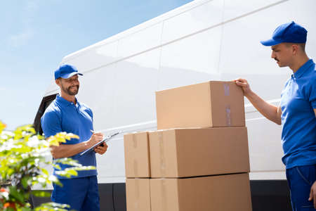 Van Courier And Professional Movers Unload Truck Stock Photo