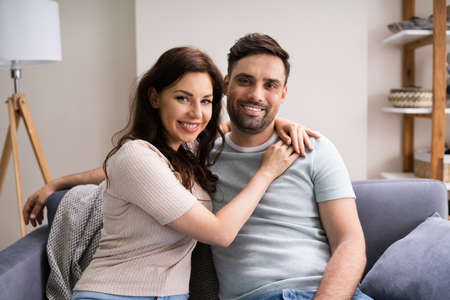 Sitted Happy Man And Woman On Sofa Or Couch At Home