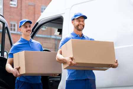 Truck Movers Loading Van Carrying Boxes And Moving House Stock Photo
