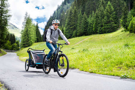 Man With E Bike MTB And Kid Trailer Training