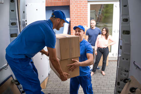 Happy Family Couple Watching Movers Unload Boxes From Truck