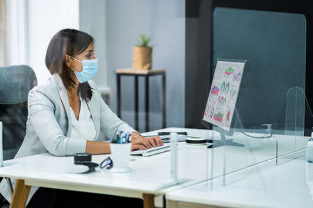 Employee In Office Social Distancing Using Sneeze Guard And Face Mask
