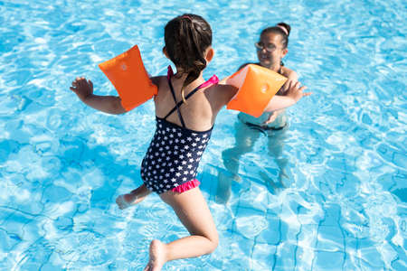 Child Jumping In Swimming Pool In Summer