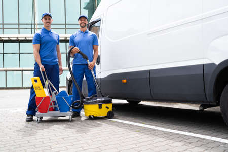 Guy With Vacuum Cleaner And Worker Near Truck