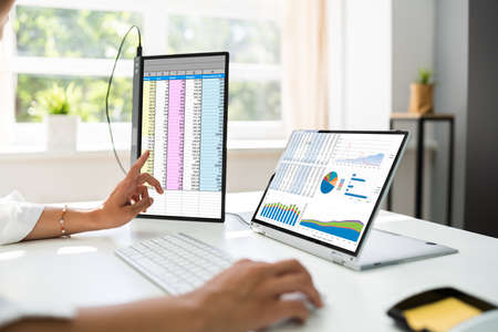 Analyst Employee Working With Spreadsheet Report On Screen