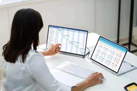 Employee Working On Calendar Schedule And Staff Time Sheet Foto de archivo