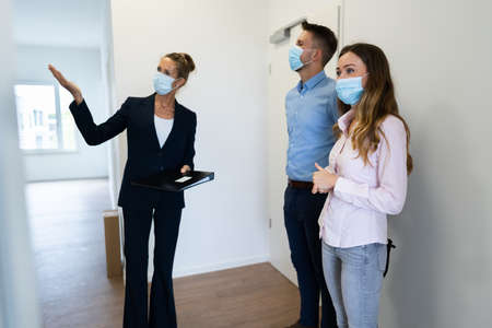 Happy Couple Buying New Home With Realtor Wearing Face Masks Stock Photo