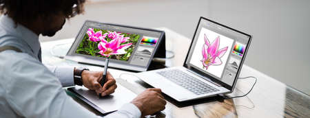 African American Designer Using Laptop Computer In Office Stock Photo