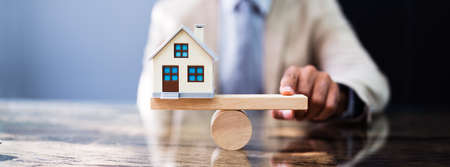 Wooden Seesaw House Balance. Real Estate Leverage