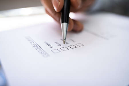 African American Hand Marking Check Mark In Checklist Survey