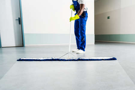 Close-up Of Man Cleaning The Floor At Office Or Workplace