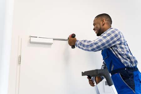 African American Man Installing And Fixing Door Closer Фото со стока