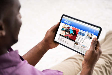 Watching News On Tablet Computer Screen Online At Home