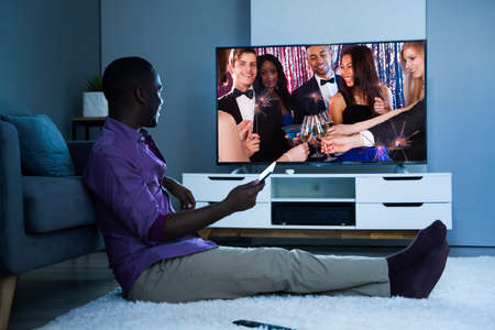 Large Version Of African Man Watching TV Movie Or Television Archivio Fotografico