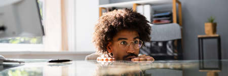 African American Sneaky Man Avoiding Work In Office