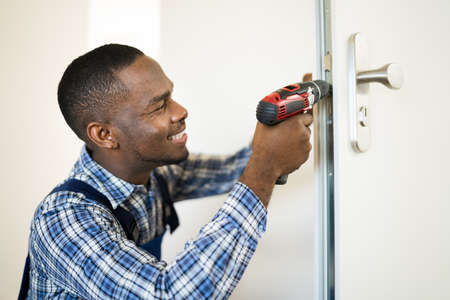 African Locksmith Man Changing And Fixing Door Lock