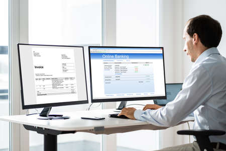 Young Businessman Looking At Invoice While Doing Online Banking On Computer