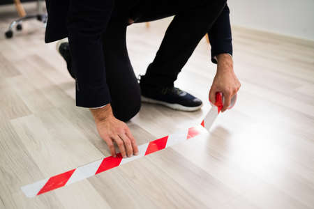 Business Employee Using Red Tape Mark For Prevention And Social Distancing In Office