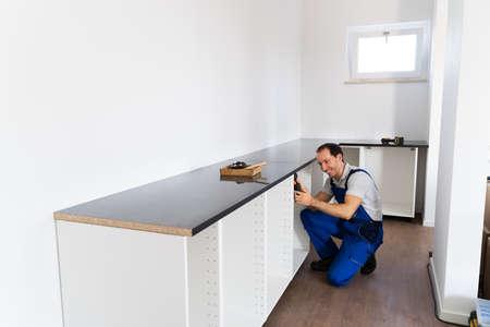 Carpenter Installing Kitchen. Handyman Cabinet Furniture Installation