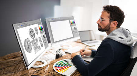Designer Editing Photos On Multiple Computer Screens