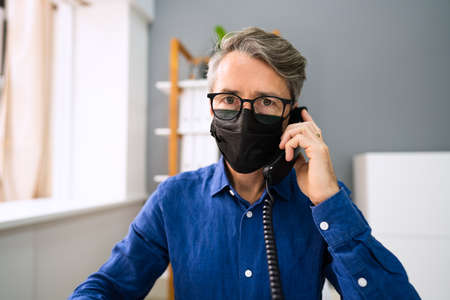 Business Man Talking On Phone Or Telephone In Mask