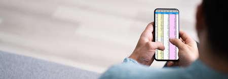Analyst Employee Using Spreadsheet On Mobile Phone Screen