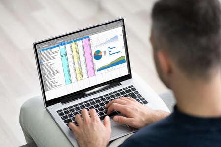 Man Using Spreadsheet Data On Laptop Computer