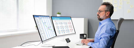 Employee Using Schedule Calendar On Computer Screen