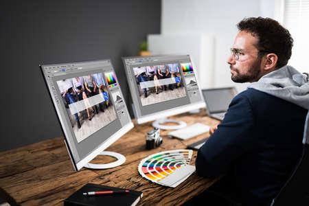 Designer Editing Photos On Multiple Computer Screens 免版税图像