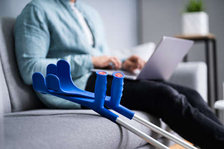 Injured Man With Broken Leg And Crutches Using Laptop 免版税图像
