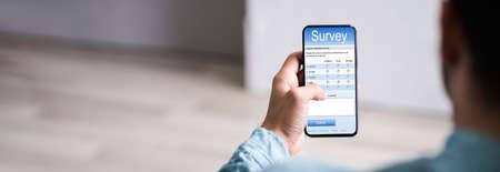 Man Filling Online Survey Form On Mobile Phone