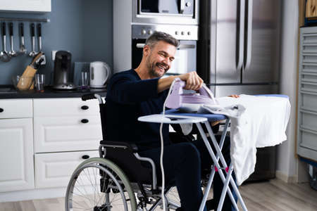 Handicapped Disabled Man In Wheelchair Ironing Clothes