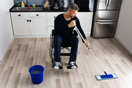 Handicapped Disabled Man Cleaning Kitchen Floor Using Map