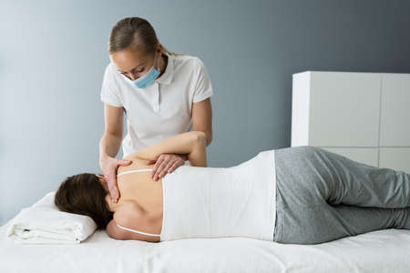 Rehab Shoulder Treatment By Sports Masseur And Physiotherapist In Face Mask Stock fotó