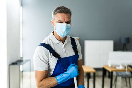 Male Janitor Mopping Floor In Face Mask In Office