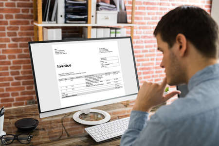 Businessman Checking Invoice On Computer At Workplace