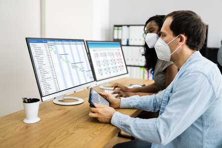 Using Gantt List Planner On Computer Wearing Face Mask