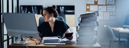 Young Businesswoman Working At Office With Stack Of Folders On Desk