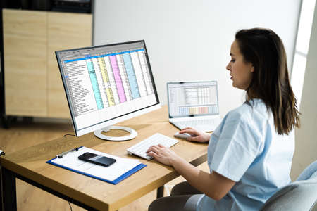 Medical Bill Codes And Spreadsheet Data. Business Analyst Woman Stock Photo