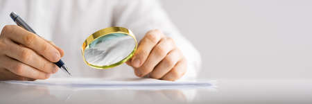 Fraud Investigation Through Magnifying Glass. Businessman Holding Loupe