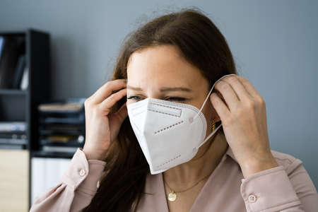 Woman Putting On Medical FFP2 Face Mask Stock Photo