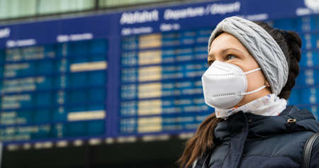 Departure Schedule Behind Woman In Face Mask